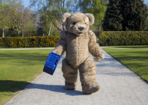 Larger than life teddy bear mascot Bentley the bear out for a stroll in the park