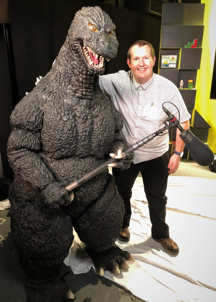 Special Effects Coordinator Matt and Godzilla pose for a photo at SYFY Wire NY
