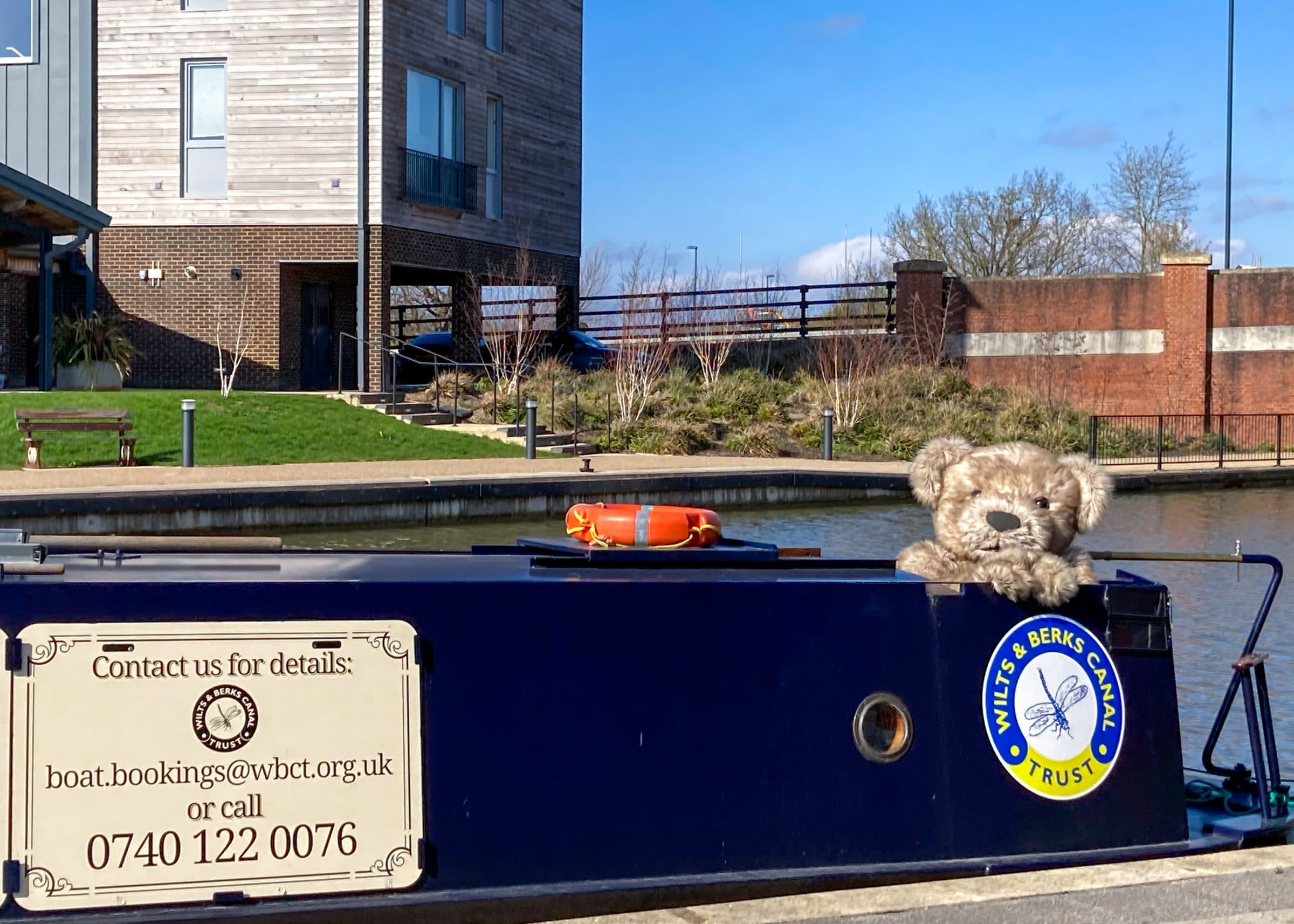 Bentley the Bear, a realistic teddy bear costume posing on the Dragonfly, a narrowboat.